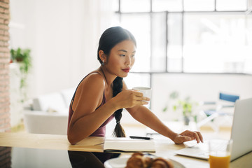 Woman with cup of coffee working with laptop at home
