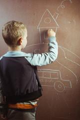 little boy draws with chalk on a blackboard,