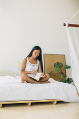 Young woman sitting on bed reading book