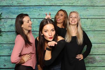 4 hübsche Mädchen albern vor einer Fotobox herum - Lachen und Luftküsse mit Photobooth