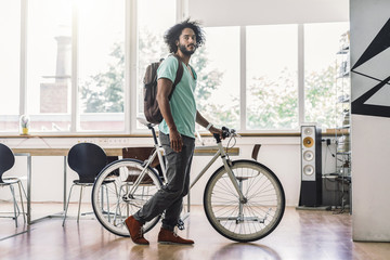 Young man with rucksack pushing bicycle in office