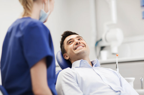 female dentist with happy male patient at clinic