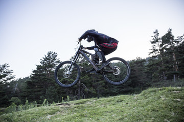Mountainbiker riding downhill jumping midair