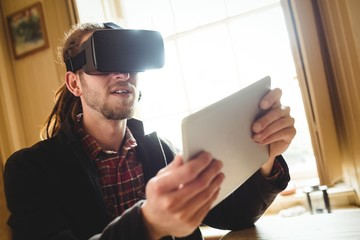 Young man holding tablet while using virtual reality simulator