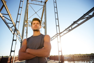Sports man resting after running with hands crossed on bridge