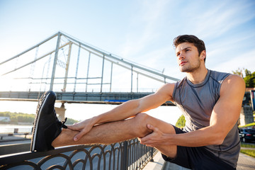 Sports man doing stretching leaning against the bridge railing