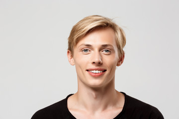 Close up portrait of cheerful smiling blond handsome young man wearing black t-shirt isolated on grey background