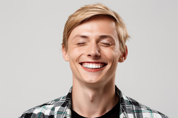 Close up portrait of handsome blond young man wearing casual plaid shirt smiling with eyes closed isolated on grey background