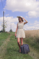 woman with suitcase at the field edge