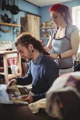 Yong woman braiding hair of hipster man