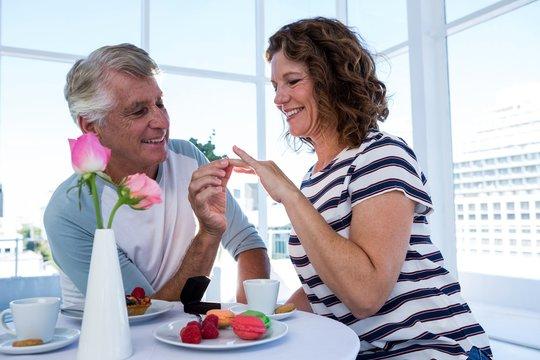 Mature man gifting ring to woman