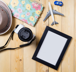Empty picture frame in Summer vacation theme. Traveler equipment with empty photo frame on wooden desk.