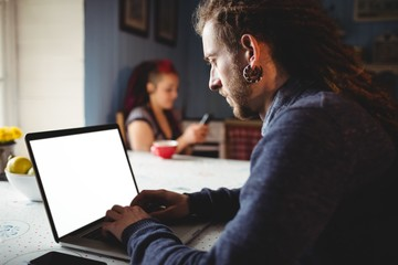 Man using laptop while woman sitting at home