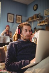 Man using laptop while listening music at home