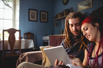 Young couple using digital tablet while sitting at home