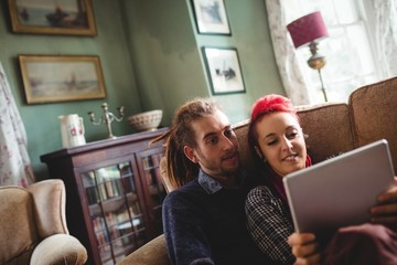 Couple using digital tablet on sofa