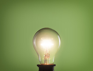 Glowing light bulb on green background