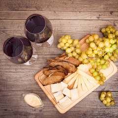 Cheese, toasted brown bread, two glasses of red wine. Horizontal.