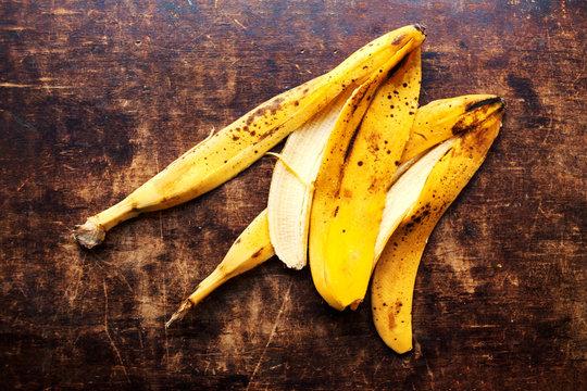 A branch of rotten ripe bananas peel  on vintage wooden backgrou