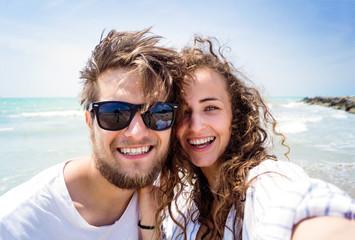 Beautiful couple on beach, laughing, taking selfie, smiling