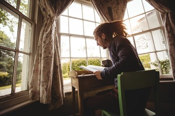 Young man reading book by window at home