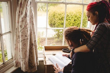 Young couple reading book by window