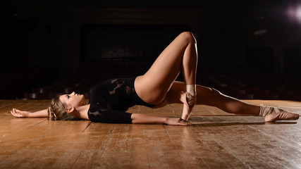 ballerina in pointe shoes is lying her back bent leg