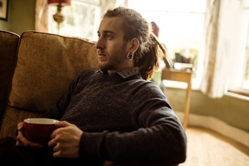Hipster holding coffee cup while relaxing on sofa