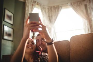 Couple taking selfie while sitting on sofa