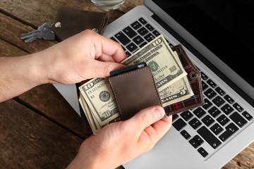 Fototapeta Man hands with laptop and wallet on wooden table