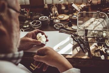 Hands of horologist repairing a watch