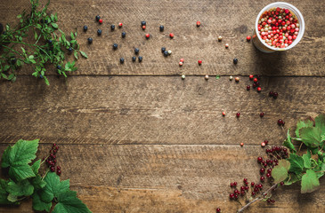 Composition with bilberries, red currant with leaves in the old wooden impressive boards. Natural light shadows