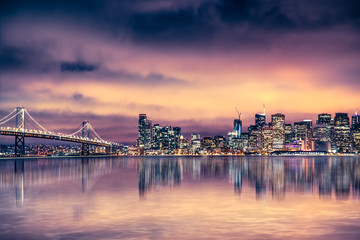 San Francisco California skyline with lights and bay under colorful sunset sky
