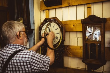 Rear view of horologist repairing a clock hung on wall