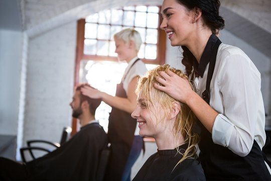 Smiling hair stylist massaging clients hair