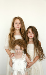 three little girls in vintage clothing