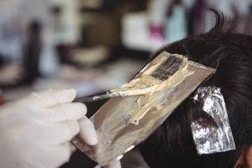 Hairdresser dyeing hair of client