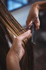 Hairdresser trimming hair of female customer in salon