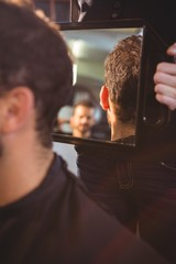Hairdresser showing man his haircut in mirror