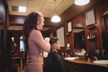 Female barber styling customer hair