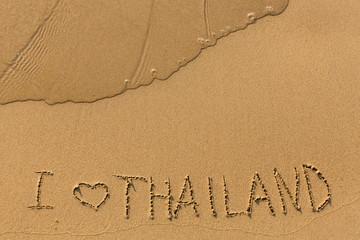I love Thailand - inscription on a golden sand beach with a gentle surf.
