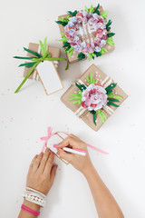 Gifts in colorful festive packaging with flowers and ribbons.