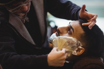 Man getting his beard shaved with shaving brush