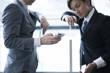 Young businessman has been the stand talking while looking at the smartphone