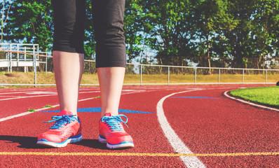 Female athlete standing on a stadium track