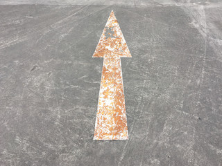 Old painted arrow sign on road.