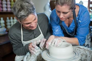 Male potter assisting female potter