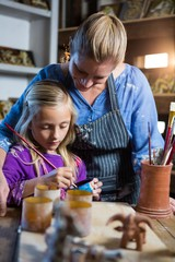 Female potter assisting girl in painting