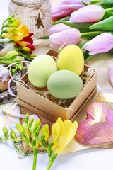 Easter decorations: colorful eggs in paper box, spring flowers a