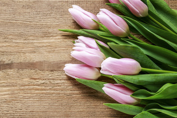 Beautiful pink tulips on wooden background